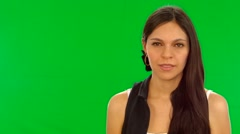 Attractive brunette model acting insecure, standing in front of green screen. Stock Footage
