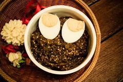 Thai food pound eggplant with boiled egg on wood table , vintage style Stock Photos