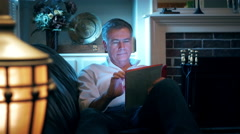 man reclining on his couch using an electronic tablet 4k - stock footage