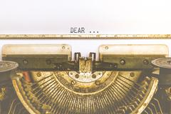 Typewriter and empty white paper with a word Dear, vintage style - stock photo
