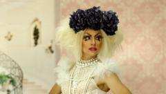 Drag queen with a glamorous look enters camera frame and posing quickly. - stock footage
