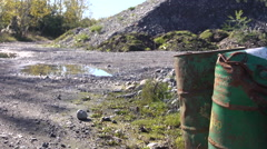 Oil drums waste away in quarry Stock Footage