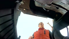 Man mechanic repairing a car engine turns the key Stock Footage