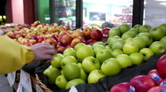 Woman selecting green apple in grocery store - stock footage