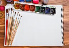 Album for sketches, watercolor paints and brushes - stock photo