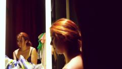 Beautiful young red-haired woman trying on dress in front of mirror in dressing Stock Footage