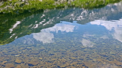 Reflection of mountain hills in the crystal water of a mountain lake Stock Footage