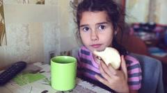 Teen girl eats bread with butter tea drinkers breakfast Stock Footage