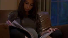 Close up of pregnant woman reading magazine Stock Footage