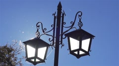 Old street lamp lit during the day spectacular sunlight Stock Footage