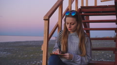 Travel: beautiful girl tourist drawing sunset at the beach. Medium shot, slow Stock Footage