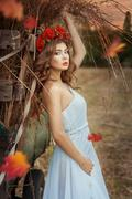 Pretty girl leaning on a hay wagon. Stock Photos