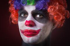 Evil Spooky Clown Portrait on dark background. expressive man Stock Photos