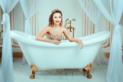 Girl with crown lies in the bath and smiling. Stock Photos