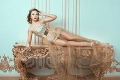 Fashionable woman lies on an expensive antique table. - stock photo