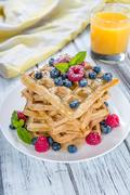 Fresh made Waffles with mixed Berries and Honey - stock photo