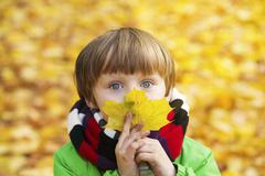 boy in park in the fall with a leaf - stock photo