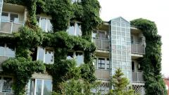View of the overgrown prefab house by plants in the suburb Stock Footage