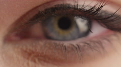 Close-up focusing shot of a woman's blue eye from the front with light make-up Stock Footage