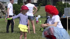 Entertainer personage with red wig blow soap bubbles with cute girl. 4K Stock Footage