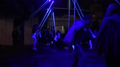 Young people swing on rope swings on neon light at night. 4K Stock Footage