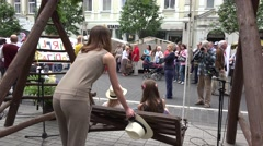 Stock Video Footage of woman roll girls on swing and people recreate in outdoor fair. 4K
