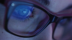 Close-up shot of woman eye in glasses staring at a working tablet screen - stock footage