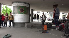 Stock Video Footage of rock musician play in open space of the city for crowd people. 4K