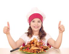 happy little girl cook with roasted chicken drumstick and thumbs up - stock photo