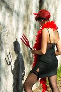 Woman devil looks at his shadow - stock photo