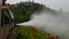 Steam train emitting white vapor, drives through a valley Stock Footage