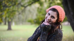 Portrait of an attractive young woman wrapping up on a fresh autumn day - stock footage