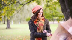 Beautiful young woman open umbrella and rotates it - stock footage