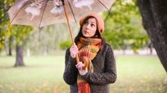 Beautiful young woman rotates umbrella - stock footage