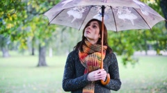 Beautiful young with umbrella and rotates it - stock footage