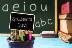 pencil crayons and text students day in a chalkboard - stock photo