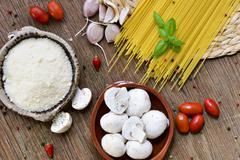 grated cheese, garlics, mushrooms, cherry tomatoes and spaghetti - stock photo