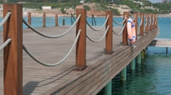 Scene of calm bathing place with emty wooden stage with ropes and lifebuoy and Stock Footage