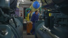 Maintenance worker amidst old-style air-conditioning chiller plant Stock Footage