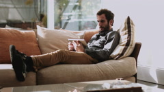 Adult man lying on the couch and using digital tablet Stock Footage