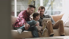 Same sex couple family on the couch using digital tablet Stock Footage