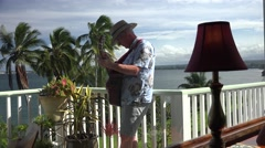 Man playing the guitar on the Lanai  Hawaii Stock Footage