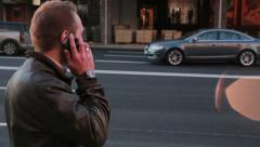 Young man talking on the phone on the street Stock Footage