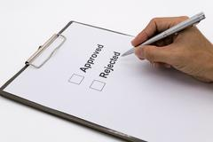 Man hand with pen over document, select Approved or Rejected. - stock photo