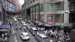 Busy people and cars outside a small commodity market Stock Footage