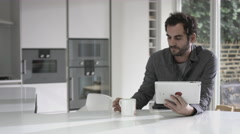 Adult male working on digital tablet and drinking coffee at home - stock footage