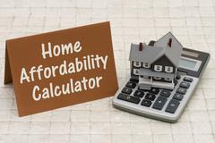 Stock Photo of Home Mortgage Affordability Calculator, A gray house, brown card and calculat
