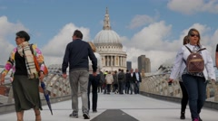 Pedestrians walking across the Millennium Bridge Stock Footage