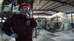 Industrial worker in manufacturing plant using radio communication Stock Footage