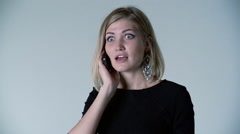 Girl surprised on the phone white background Stock Footage